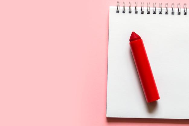 Красные фломастеры на белом листе доски со спиралью на нежно-розовом