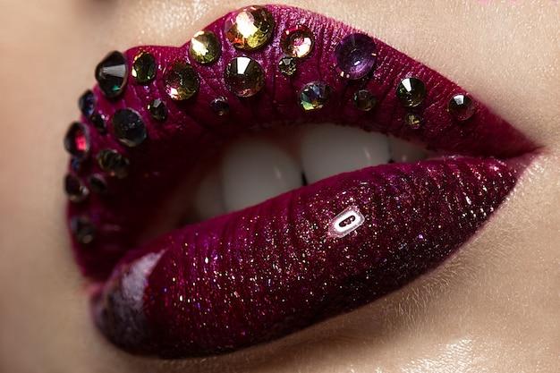 Red female art lips with rhinestones closeup.