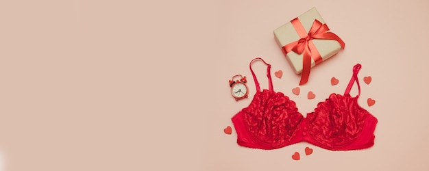 Red female underwear with a festive box with a red bow ribbon