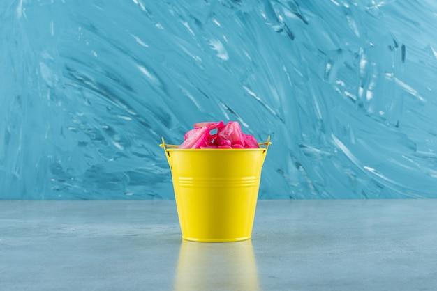 파란색 테이블에 양동이에 붉은 발효 소금에 절인 양배추.