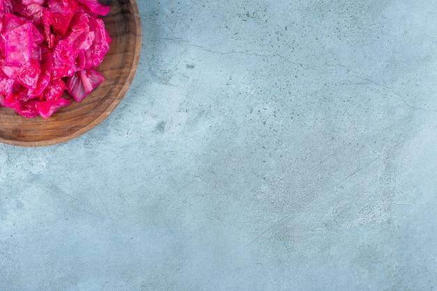 Красная квашеная капуста на деревянной тарелке, на синем столе.