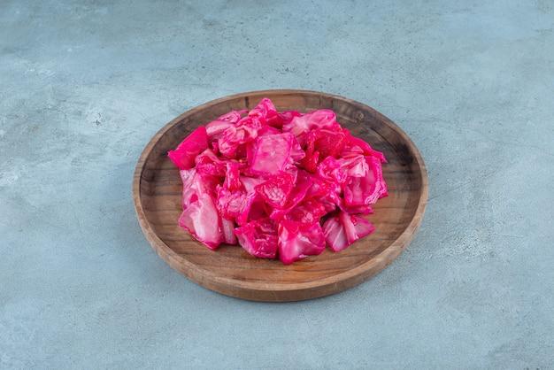 파란색 테이블에 나무 접시에 붉은 발효 소금에 절인 양배추.