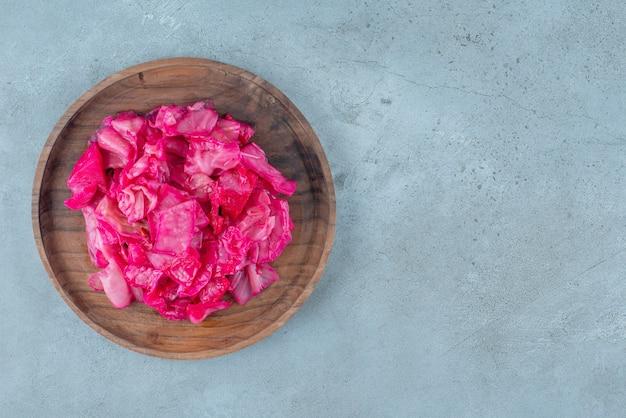 青いテーブルの上に、木の板の上に赤い発酵ザワークラウト。