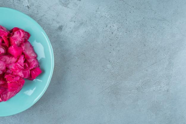 파란색 테이블에 접시에 붉은 발효된 소금에 절인 양배추.