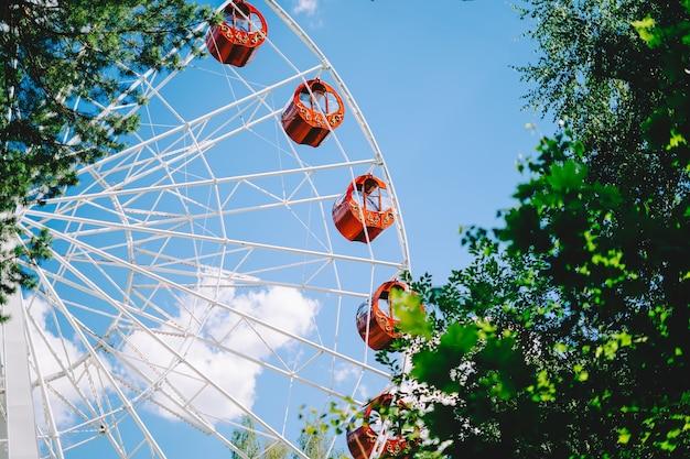 Красное колесо обозрения над голубым небом и зелеными листьями Premium Фотографии