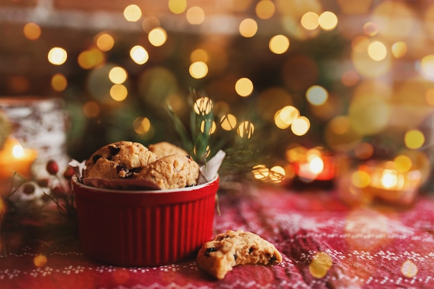 Red festive bowl full with christmas cookies blurred christmas fir tree lights