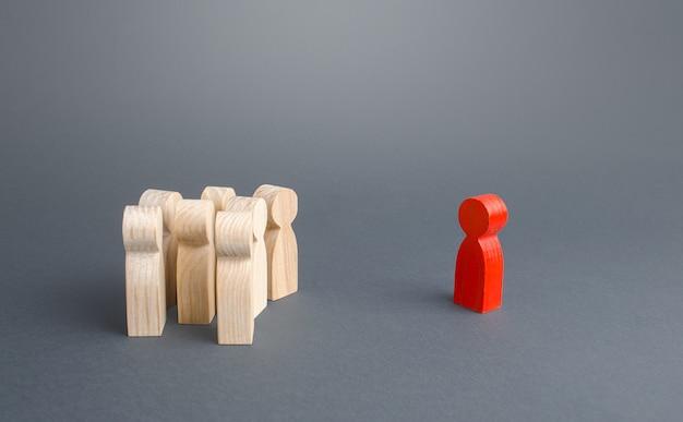 Красная фигурка человека и толпа людей, стоящих отдельно. лидерские и лидерские качества