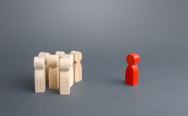 Red figurine person and crowd of people standing separately. leader and leadership skills