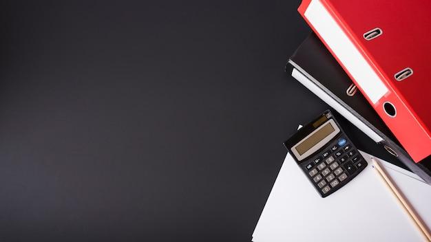 Красный файл; калькулятор; карандаши и белые документы на черном фоне