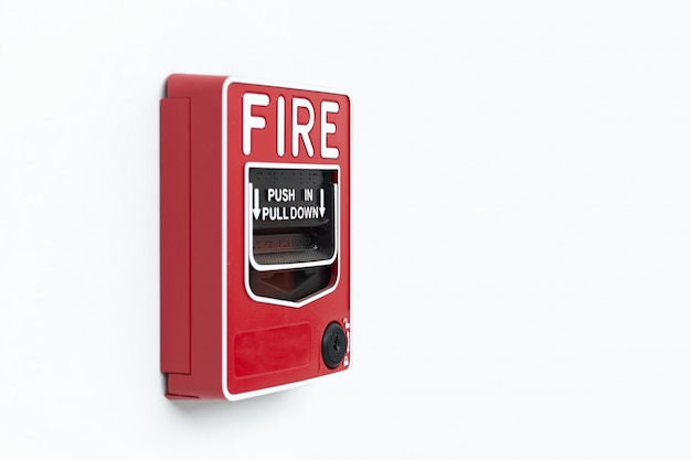 Red fire alarm box on white background inside building, alarm device.