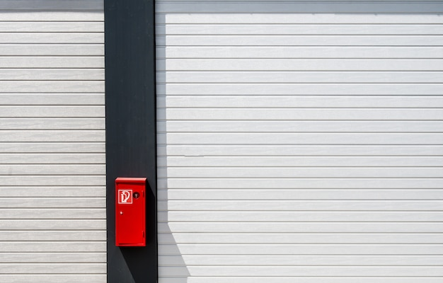 Red fire box hung on a black and white surface with lines