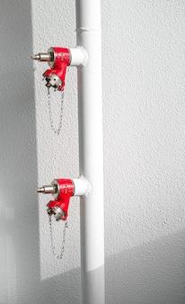 Красный огнетушитель на белой стене