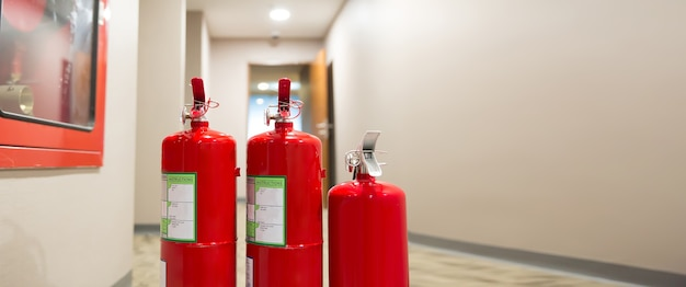 Red fire extinguishers tank at the exit door in the building