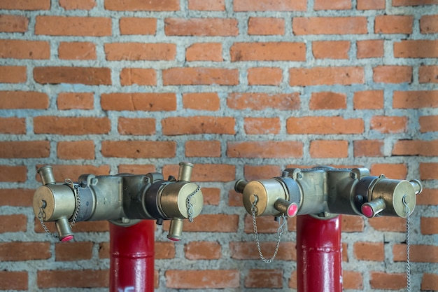 Red fire hydrant water pipe against bricks wall.