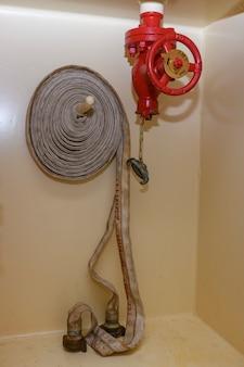 コイル状のホースが付いている赤い消火栓。消火機器。