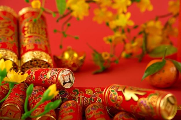 中国の旧正月のお祝いのために準備された赤いテーブルに最高の願いの碑文、アプリコットの流れとみかんが付いた赤い爆竹