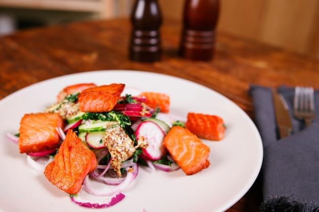 무와 시금치를 곁들인 붉은 생선 연어는 나무 테이블에 있는 하얀 접시에 제공됩니다. 소박한 스타일. 위에서 보기, 최고 스튜디오 촬영
