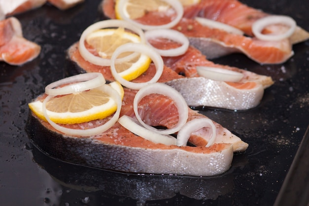 Red fish steaks ( salmon or trout ) with lemon, salt, herbs on black background.