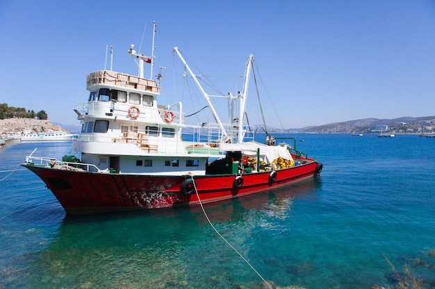 A red fishing boat sit at dock on a warm summer day in turkey kusadasi
