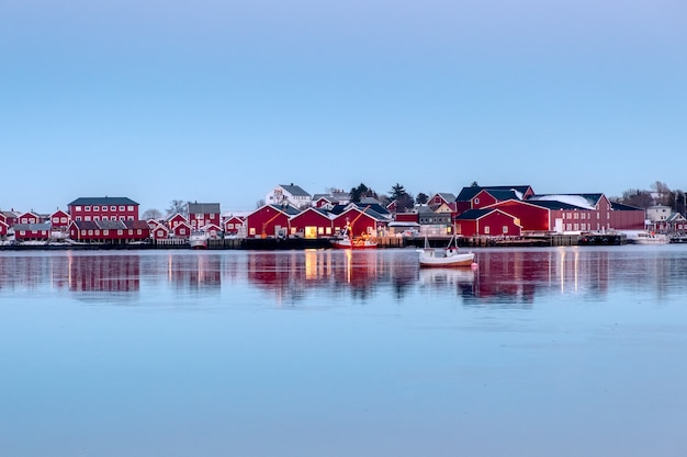 Red fishing warehouse with fishing boat reflection on coastline