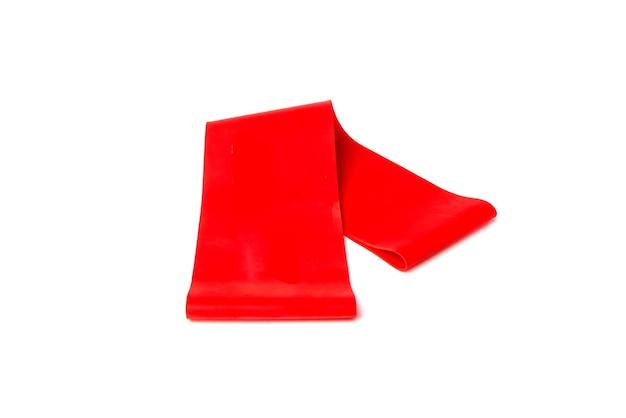 Красная фитнес-резинка для спорта на белом фоне.