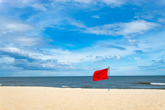 Red flag embroidered on the beach by the sea.