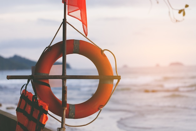 Red flag, life buoy with life jacket, warning symbol, hazard of water play