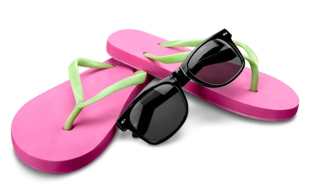 Red flip flops and sunglasses on white