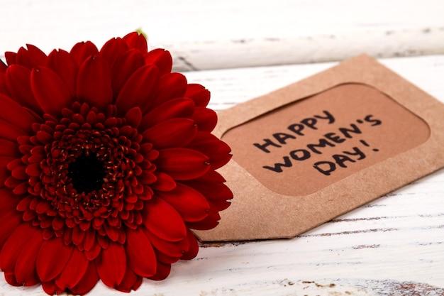 赤い花と挨拶タグの女性の日ラベルとガーベラプレゼントを作るための簡単なヒント