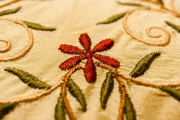 Red flower, green leaves and stems with curls, embroidered with satin stitch.