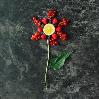 붉은 건강 식품, 과일 및 야채로 만든 붉은 꽃은 어두운 돌 벽에 녹색 잎이 있습니다. 자연 식품 개념. 평평하다.