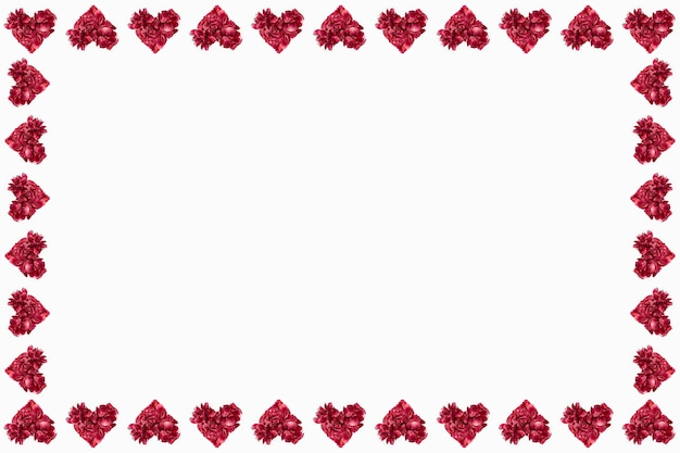 Red flower petals in shape of hearts on white surface