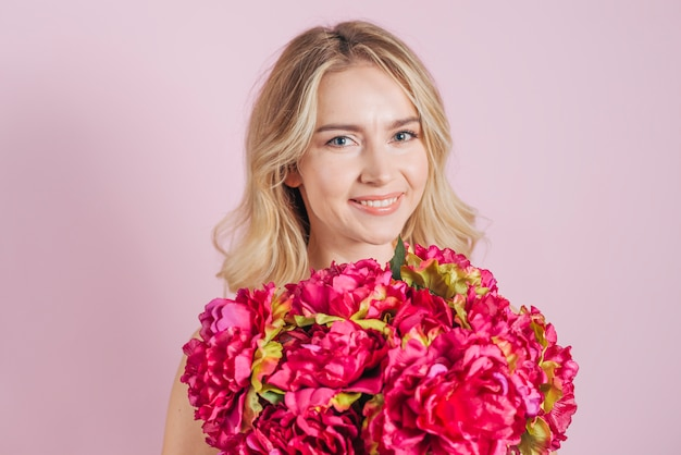 Red flower roses bouquet in front of smiling young woman against pink backdrop