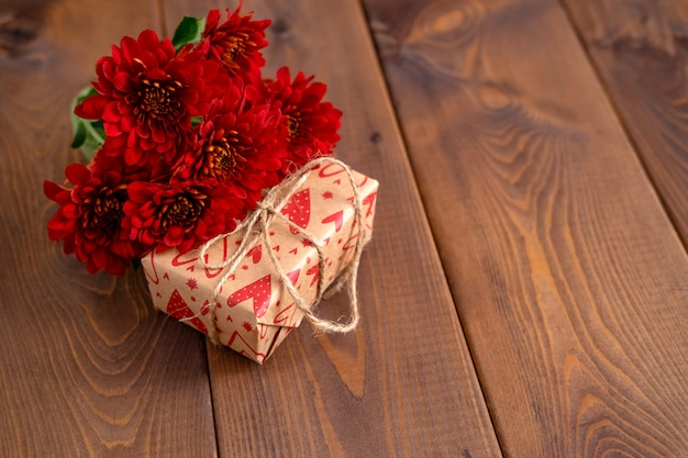 Red flowers and craft gift on wooden board. valentines day background. st.valentines day card concept