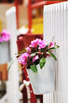 Red flowers in a decorative bucket hanging on a raft.