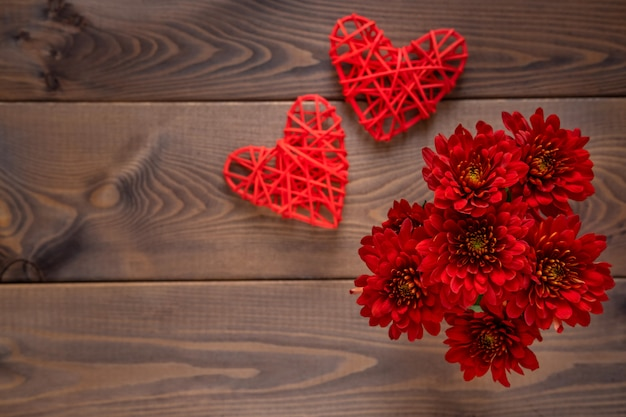 Red flowers and a hearts on wooden board. valentines day background. st.valentines day card concept