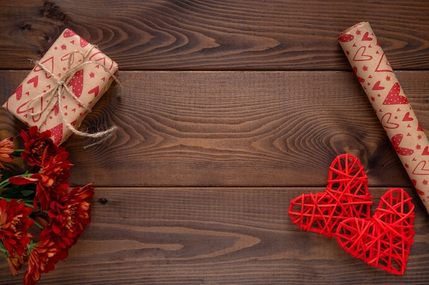 Red flowers and a hearts on wooden board. valentines day background. st.valentines day card  with copy space for text.