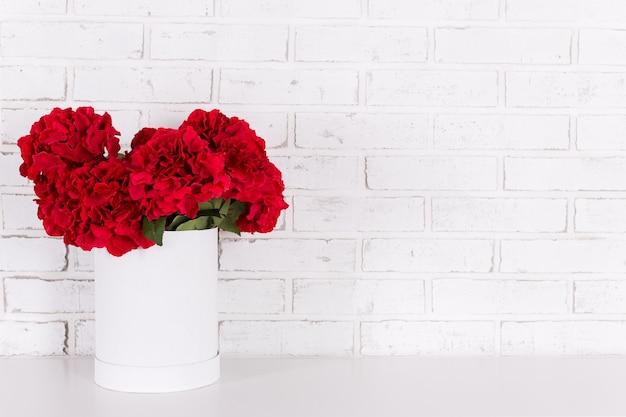 白いレンガの壁の上のテーブルの花瓶に赤い花