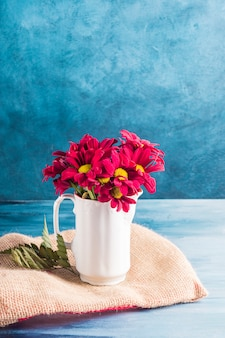 Red flowers in jug on canvas