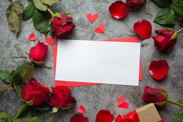 Red flowers of rose and envelop on dark background