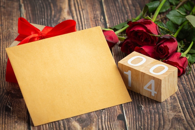 Red flowers of rose and envelop on on dark wood background