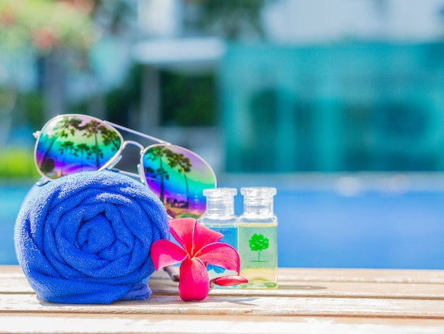 Red flowers, sunglasses, shampoo, lotion and rolled up towels at the side of swimming pool