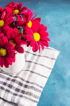 Red flowers in vase on cloth