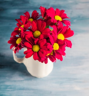 Red flowers in vase on grey table