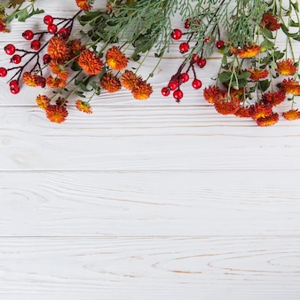 Red flowers with berries scattered on wooden table