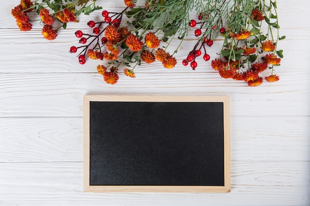 Red flowers with blank chalkboard on white table