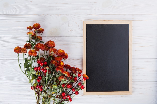 Red flowers with blank chalkboard on wooden table