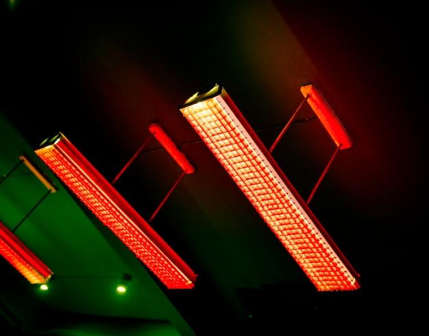 Красная люминесцентная лампа, свисающая с потолка