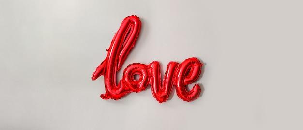 灰色の背景に赤いホイル気球の碑文。縦の写真。バレンタイン・デー