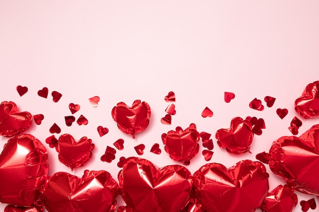 パステルピンクの背景にハート形の赤い箔風船。バレンタインの休日のお祝いや結婚式パーティーの装飾背景